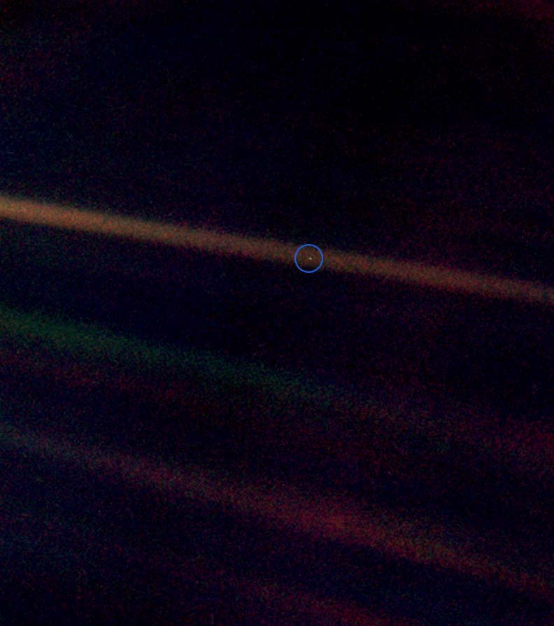 "This is the ""Pale Blue Dot"" photograph of the Earth taken by the Voyager 1 spacecraft on July 6, 1990. The Earth is the relatively bright speck of light about halfway across the uppermost sunbeam. (shown here inside a blue circle)"